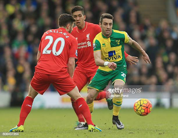 Ivo Pinto of Norwich City and Adam Lallana of Liverpool compete for the ball during the Barclays Premier League match between Norwich City and...