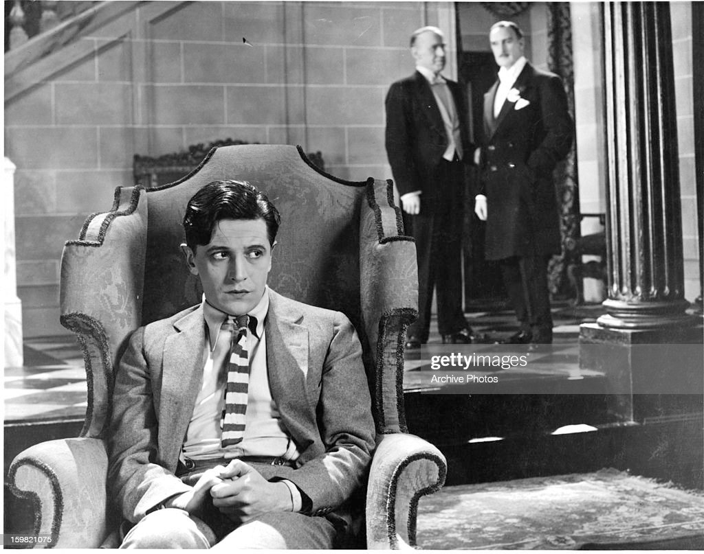 Ivor Novello slumps in a chair in a scene from the film 'When Boys Leave Home' 1927