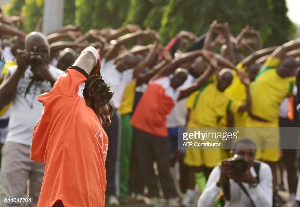 Ivorian athlet MarieJosee TaLou leads a warmup exercice as she takes part in the 'Ivorian army cohesion day' on September 8 2017 in Abidjan / AFP...