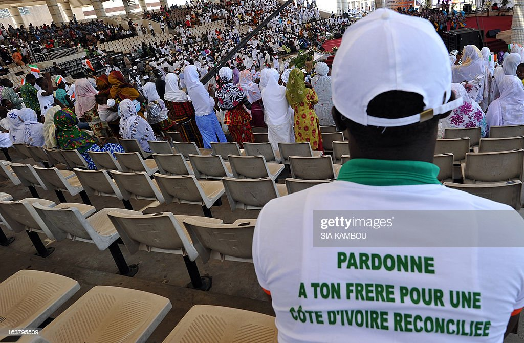 Ivorian Christians and Muslims pray on March 16, 2013 at the culture palace in Abidjan during the official launch of the days of prayer for repentance, reconciliation, unity, love and peace in Ivory Coast. Writing on T-shirt reads: 'Forgive your brother for a reconciliated Ivory Coast'.