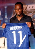 Ivorian football star Didier Drogba holds up a team shirt during a press conference to announce his move to Shanghai Shenhua FC at RitzCarlton Hotel...