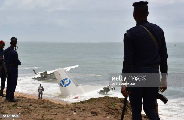 Ivorian Gendarmes stand on the beach of PortBouet in Abidjan near the wreckage of a cargo plane that crashed off Ivory Coast killing four on October...