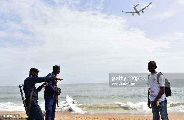 Ivorian Gendarmes stand on the beach of PortBouet in Abidjan near the wreckage of a cargo plane that crashed off Ivory Coast killing four as a plane...