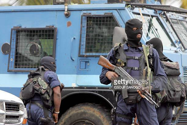 Ivorian hooded gendarme officers escort the van carrying French alleged gang leader Youssouf Fofana on his way to board a Parisbound plane at Abidjan...