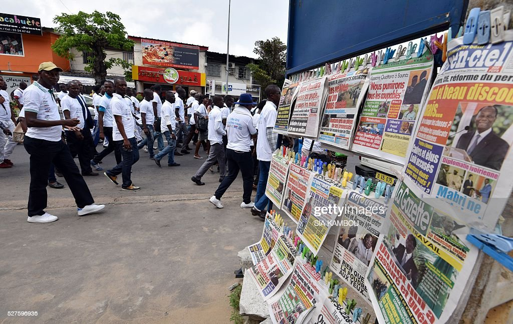 Ivorian journalists walk past newspapers displayed in a street as they take part in a march in Abidjan on May 3, 2016 for the World Press Freedom day. / AFP / Sia KAMBOU