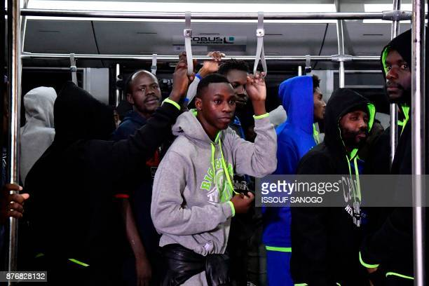 Ivorian migrants board a shuttle bus upon arrival from Libya as they return to be repatriated in their country at the airport of Abidjan on November...