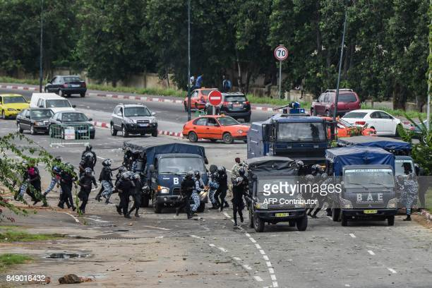 Ivorian police officers run towards their vehicles under pressure from protesting students during clashes within a demonstration against rising...