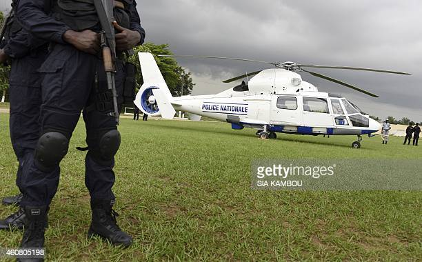 Ivorian policemen secure a helicopter handed over by the national council of security at the police academy in Abidjan on December 23 2014 within the...
