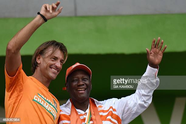 Ivorian President Alassane Ouattara and Ivory Coast's national football team coach Herve Renard wave at the crowd during a welcoming ceremony at...