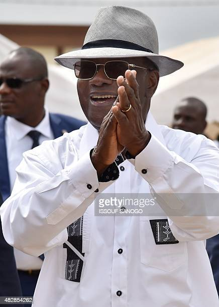 Ivorian President Alassane Ouattara applauds during a visit to the city of Dabou about 45 kms west of Abidjan on August 3 2015 Ouattara was nominated...
