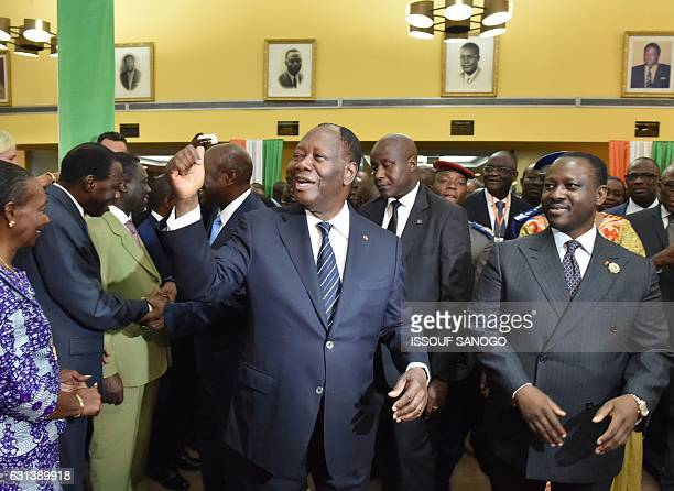 Ivorian President Alassane Ouattara flanked by newly reelected Ivorian National Assembly president Guillaume Soro gestures as he walks out after...