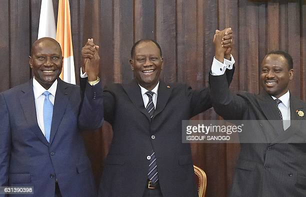 Ivorian President Alassane Ouattara holds hands of newly reelected Ivorian National Assembly president Guillaume Soro and former Ivorian prime...