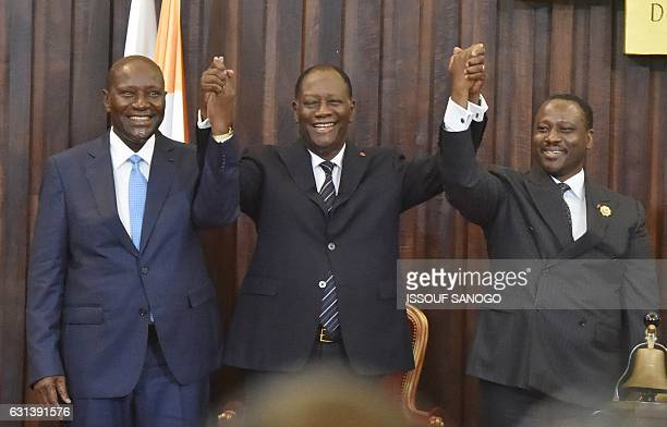 Ivorian President Alassane Ouattara holds hands of newly reelected Ivorian National Assembly president Guillaume Soro and outgoing Ivorian prime...