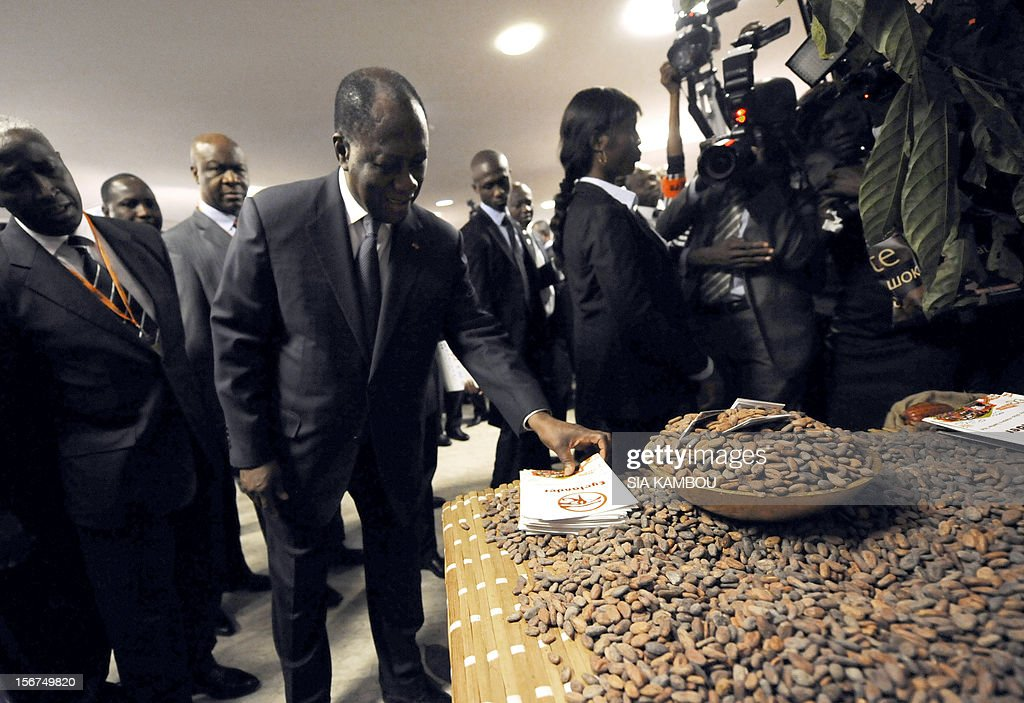 Ivorian President Alassane Ouattara (C) looks at a stand of cocoa after the opening ceremony of the 2012 World Cocoa conference in Abidjan. Ivory Coast on Tuesday hosts world players in the cocoa business for a conference on how to face up to the challenges posed by soaring demand. AFP PHOTO/ SIA KAMBOU