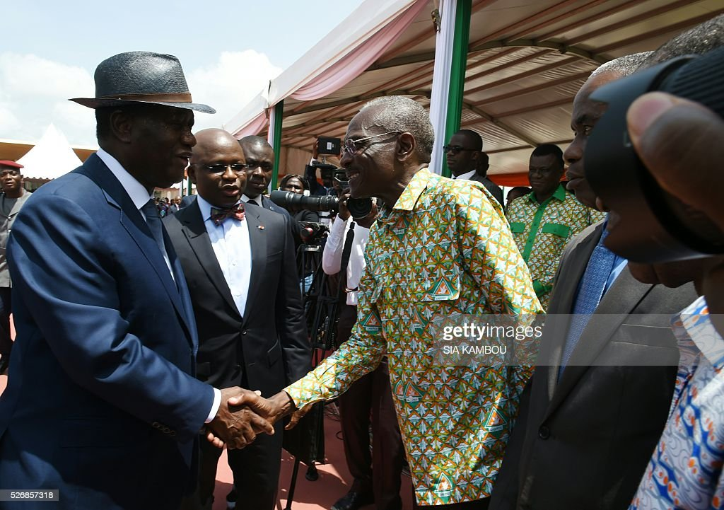 Ivorian president Alassane Ouattara shakes hands with a union representative upon his arrival at the presidential palace to take part in ceremonies marking May Day, on May 1, 2016 in Abidjan. / AFP / SIA