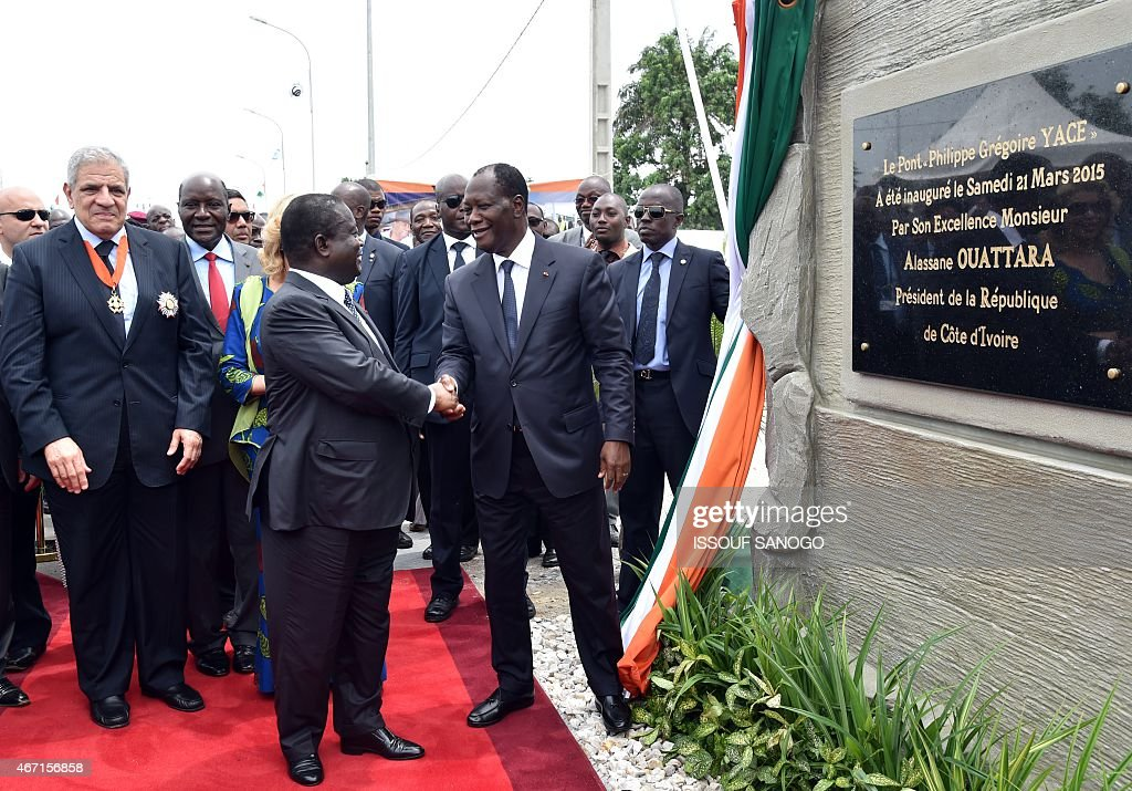 Ivorian president <a gi-track='captionPersonalityLinkClicked' href=/galleries/search?phrase=Alassane+Ouattara&family=editorial&specificpeople=697562 ng-click='$event.stopPropagation()'>Alassane Ouattara</a> (R) shakes hands with former Ivorian president <a gi-track='captionPersonalityLinkClicked' href=/galleries/search?phrase=Henri+Konan+Bedie&family=editorial&specificpeople=697544 ng-click='$event.stopPropagation()'>Henri Konan Bedie</a> (C) eyed by Egyptian Prime minister Ibrahim Mahlab (L) after unveiling a plaque during the inauguration of the Philippe Gregoire Yace bridge, on March 21, 2015 in Abidjan.
