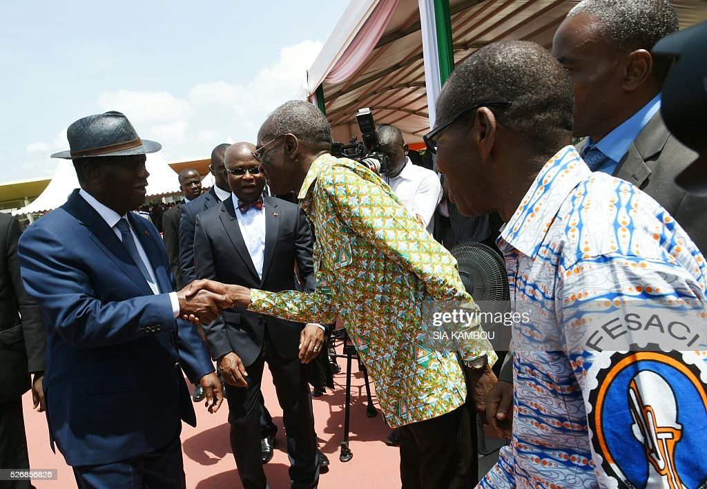 Ivorian president Alassane Ouattara shakes hands with workers upon his arrival at the presidential palace to take part in ceremonies marking May Day, on May 1, 2016 in Abidjan. / AFP / SIA