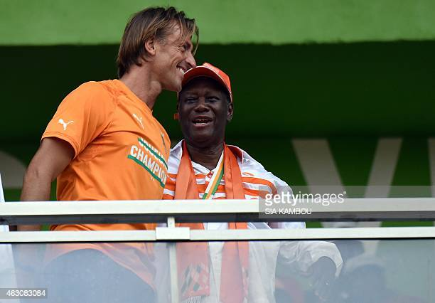 Ivorian President Alassane Ouattara speaks with Ivory Coast's national football team coach Herve Renard during a welcoming ceremony at Felix...