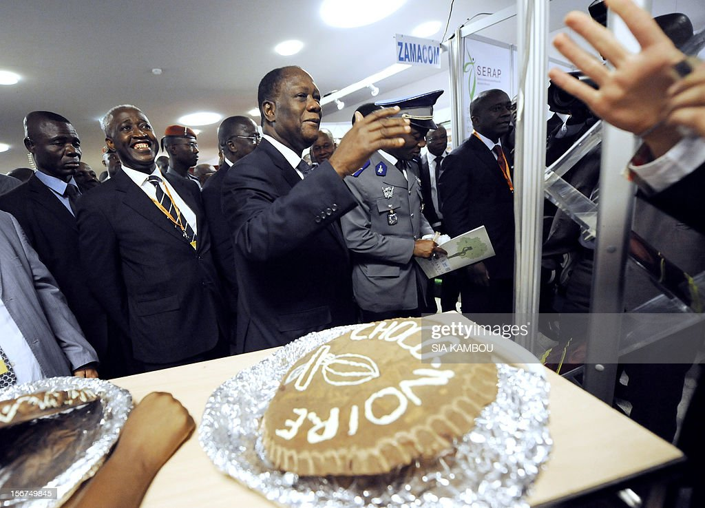Ivorian President Alassane Ouattara (C) walks past chocolate cakes after the opening ceremony of the 2012 World Cocoa conference in Abidjan. Ivory Coast on Tuesday hosts world players in the cocoa business for a conference on how to face up to the challenges posed by soaring demand. AFP PHOTO/ SIA KAMBOU