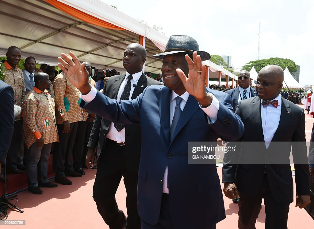 Ivorian president Alassane Ouattara waves upon his arrival at the presidential palace to take part in ceremonies marking May Day, on May 1, 2016 in Abidjan. / AFP / SIA