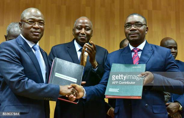 Ivorian Prime Minister Amadou Gon Coulibaly claps as Ivorian Public Service Minister Issa Coulibaly and the secretarygeneral of the InterUnion of...