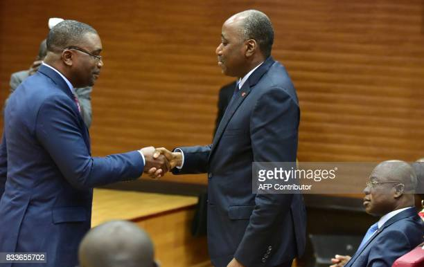Ivorian Prime Minister Amadou Gon Coulibaly shakes hands with the secretarygeneral of the InterUnion of Civil Servants of the Ivory Coast Theodore...