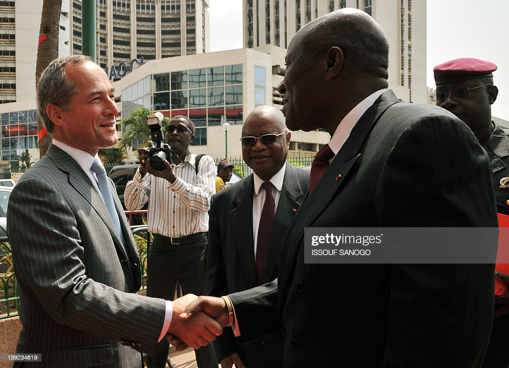 Ivorian Prime Minister Daniel Kablan Duncan (R) welcomes on January 10, 2013 the chief executive officer of French bank Societe Generale, Frederic Oudea (L), before Societe Generale de Banque in Ivory Coast (SGBCI) board chairman Tiemoko Coulibaly (C) in front of bank headquarters in Abidjan during events marking the 50th anniversary of Societe General in Ivory Coast. SANOGO