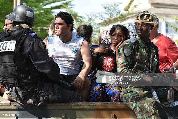 Ivorian security forces evacuate people after heavily armed gunmen opened fire on March 13 2016 at a hotel in the Ivory Coast beach resort of...