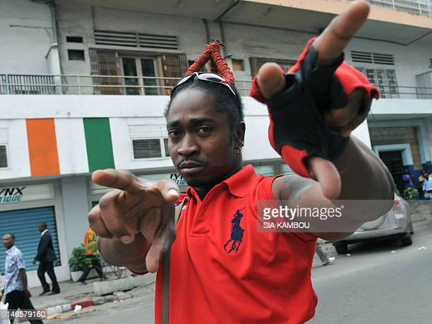 Ivorian singer and drummer Julien Goualo gestures as he sings in a street language nicknamed 'nouchi' on September 9 2009 in Abidjan Speaking nouchi...