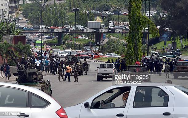 Ivorian soldiers and their vehicles block one of the main streets to the 'Le plateau' business district on November 18 2014 in Abidjan to ask for...