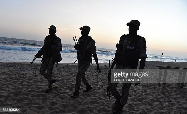 Ivorian soldiers walk on the beach after heavily armed gunmen opened fire on March 13 2016 at a hotel in the Ivory Coast beach resort of GrandBassam...