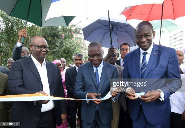 Ivorian Transport Minister Amadou Kone and director of the Ivorian Transport Company Zoumana Bakayoko cut a ribbon during a ceremony to inaugurate...