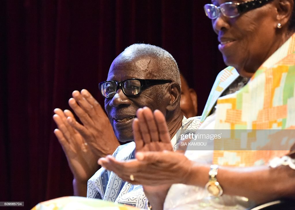 Ivorian writer Bernard Binlin Dadier (L) applauds after receiving the UNESCO-UNAM Jaime Torres Bodet prize on February 11, 2016 in Abidjan. / AFP / SIA KAMBOU