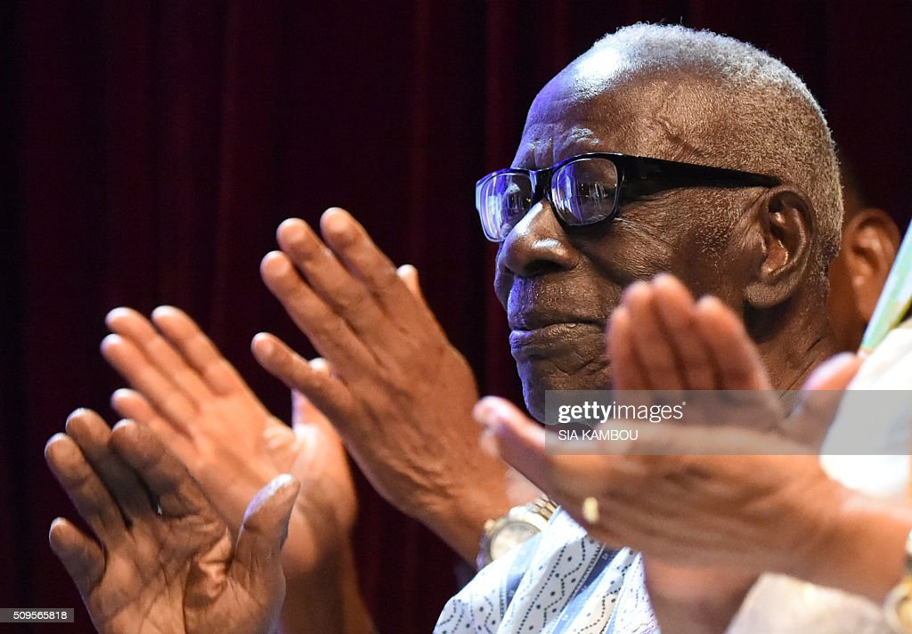Ivorian writer Bernard Binlin Dadier applauds after receiving the UNESCO-UNAM Jaime Torres Bodet prize on February 11, 2016 in Abidjan. / AFP / SIA KAMBOU