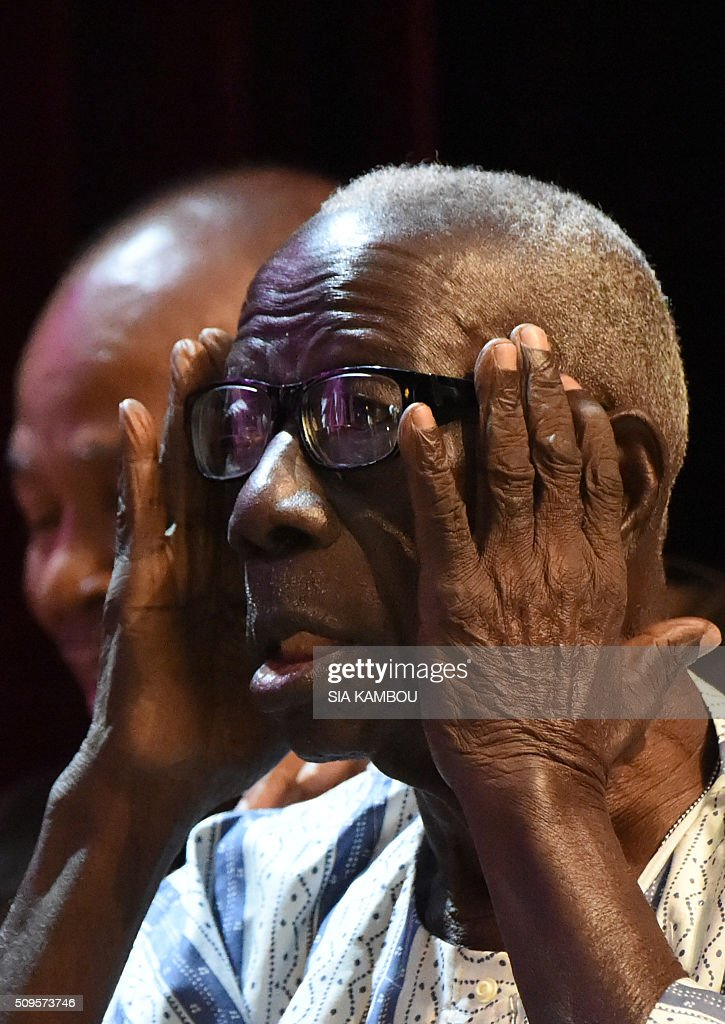 Ivorian writer Bernard Binlin Dadier adjusts his glasses after receiving the UNESCO-UNAM Jaime Torres Bodet prize on February 11, 2016 in Abidjan. / AFP / SIA KAMBOU