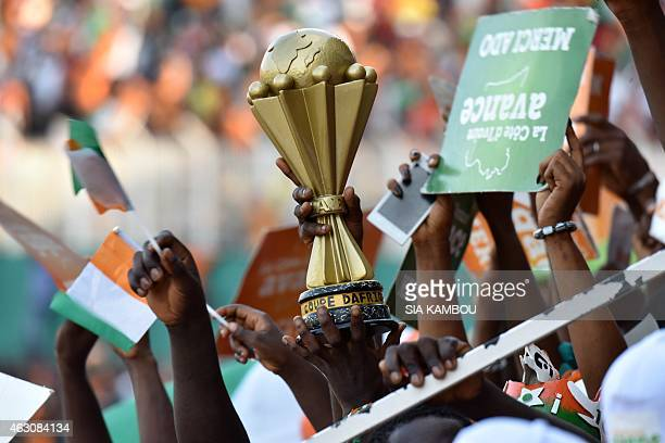 Ivorians hold a replica of the African Cup of Nations trophy as they attend a welcoming ceremony at Felix Houphouet Boigny Stadium to greet their...