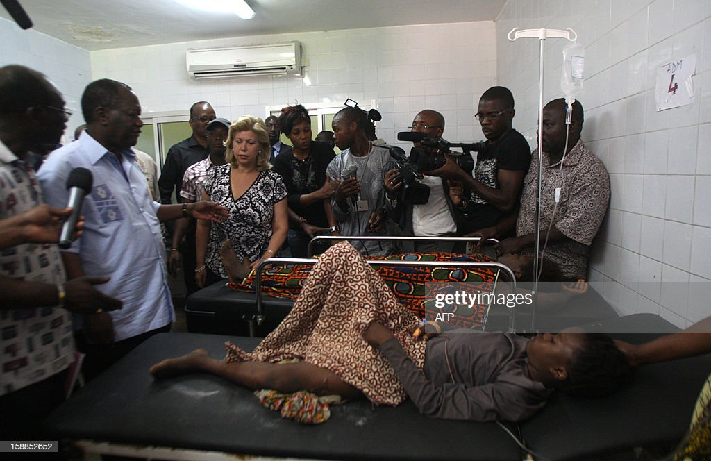 Ivory Coast Alassane Ouattara (L) and his wife Dominique (C) , stand next to a child, lying in a hospital bed after he was injured in a stampede, at the Cocody hospital in Abidjan, on January 1, 2013. At least 60 people died and at least dozens were injured as crowds stampeded overnight during celebratory New Year's fireworks, Ivory Coast rescue workers said on January 1, 2013. AFP PHOTO/HERVE SEVI