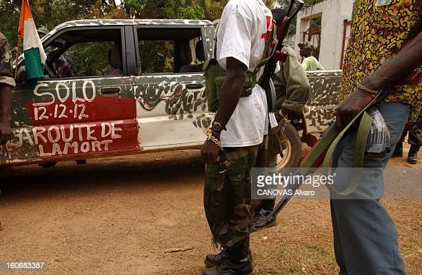 Ivory Coast At The Edge Of Chaos Miliciens libériens de l'armée loyaliste armés devant un pickup sur lequel est inscrit à la peinture blanche 'Solo...