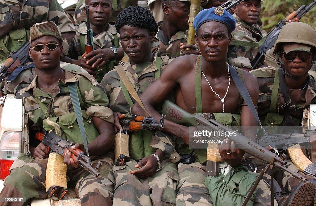 Ivory Coast At The Edge Of Chaos. Miliciens libériens de l'armée loyaliste assis avec leurs armes à l'arrière d'un pick-up dans les rue de TOULEPLEU à seulement 14 kilomètres de la frontière avec le Libéria.