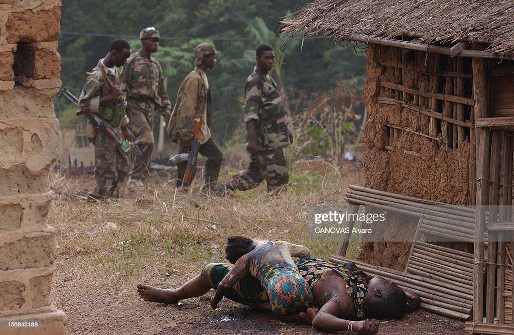 Ivory Coast At The Edge Of Chaos. Patrouille de miliciens libériens de l'armée loyaliste passant devant le cadavre d'une mère et de sa fille massacrées devant leur maison de TOULEPLEU par des rebelles battant en retraite.