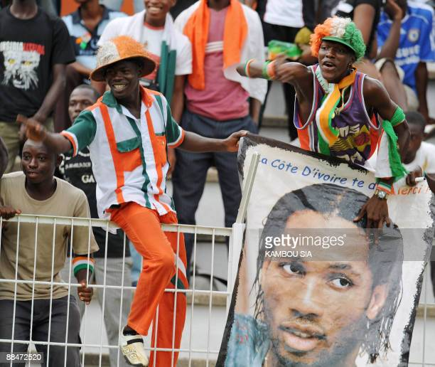 Ivory Coast Elephants' fans hold a poster of Didier Drogba during a friendly match on June 13 at the Houphouet Boigny stadium in Abidjan in memory of...