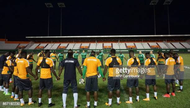 Ivory Coast footballers pray ahead of their training session at The Felix HouphouetBoigny Stadium in Abidjan on October 3 ahead of the FIFA World Cup...