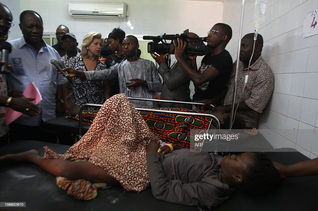 Ivory Coast President Alassane Ouattara (L) and his wife Dominique (C) stand next to a child, injured in a stampede, during a visit to the Cocody hospital in Abidjan, on January 1, 2013. At least 60 people died and at least dozens were injured as crowds stampeded overnight during celebratory New Year's fireworks, Ivory Coast rescue workers said on January 1, 2013. AFP PHOTO/HERVE SEVI