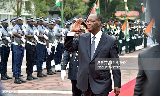 Ivory Coast President Alassane Ouattara gestures as he reviews the troops on August 7 2014 in the courtyard of the presidential palace in Abidjan...