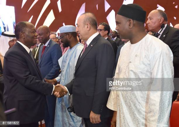 Ivory Coast President Alassane Ouattara shakes hand with Turkey's Foreign Minister Mevlut Cavusoglu as Burkina Faso's Foreign Minister Alpha Barry...