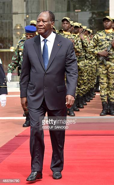 Ivory Coast President Alassane Ouattara walks as he takes part in celebrations marking the 55th anniversary of independence from France in front of...