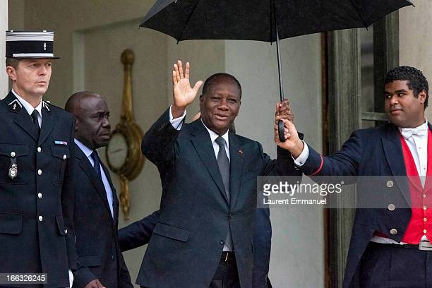 Ivory Coast President Alassane Ouattara waves as he leaves following his meeting with his French counterpart Francois Hollande at the Elysee Palace...