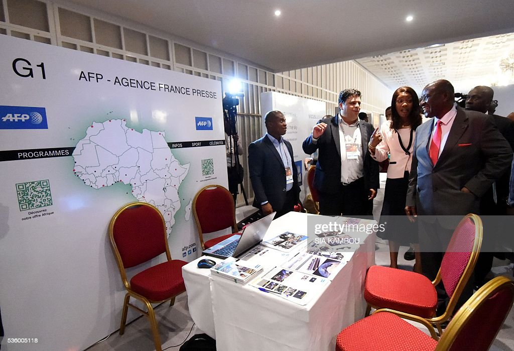 Ivory Coast prime minister Daniel Kablan Duncan (R) and communications minister Affoussiatou Bamba-Lamine(2-R) speak with Agence France Presse's (AFP) commericial director for Africa Joaquin Iturralde(2-L) during a visit to the AFP stand at the DISCOP conference in Abidjan on May 31, 2016. / AFP / SIA