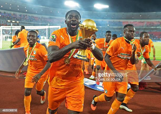 Ivory Coast's defender Kolo Toure raises the trophy as he celebrates after winning the 2015 African Cup of Nations final football match between Ivory...