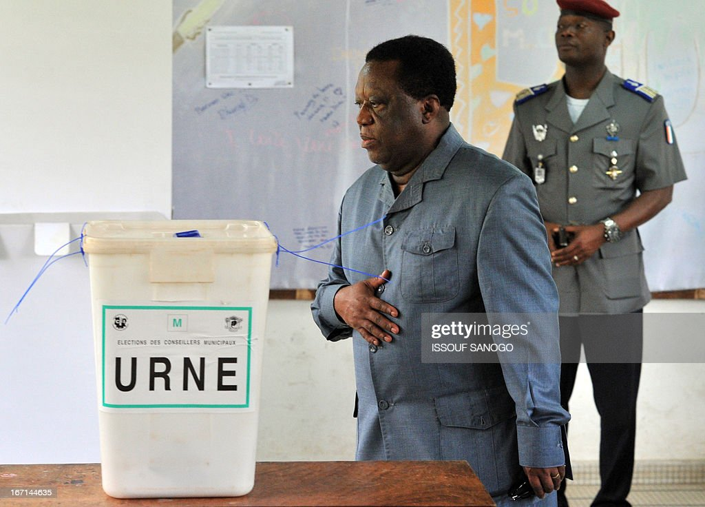 Ivory Coast's Electoral Commission president Youssouf Bakayoko walk past a ballot box at a polling station on April 21, 2013 in Abidjan. Ivorians voted today in local elections seen as a trial run for a presidential poll in 2015 amid high tensions as the party of former president Laurent Gbagbo boycotted the poll. AFP PHOTO / ISSOUF SANOGO